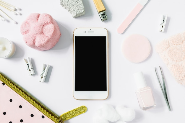 Vista elevata di smartphone circondato con vari prodotti spa sulla superficie bianca Foto Gratuite