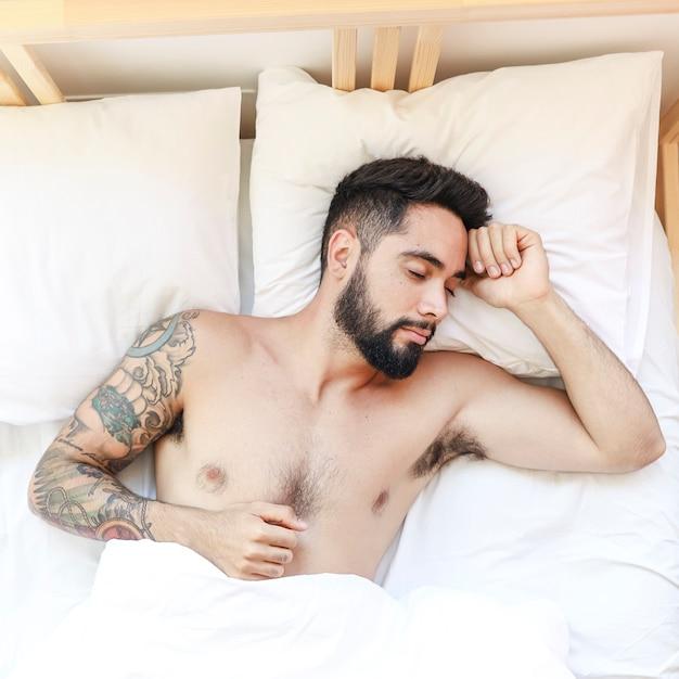 Vista elevata di un uomo senza camicia che dorme sul letto Foto Gratuite