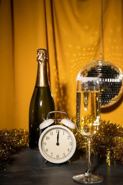 Vista frontale bottiglia di champagne e vetro Foto Gratuite