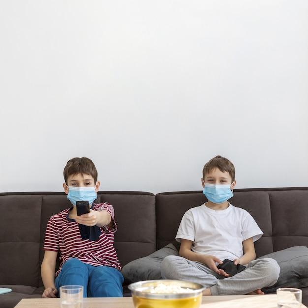 Vista frontale dei bambini con le maschere mediche che guardano tv Foto Gratuite