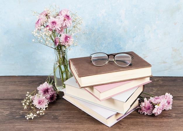 Vista frontale dei vetri sul libro e dei fiori sulla tavola di legno Foto Gratuite
