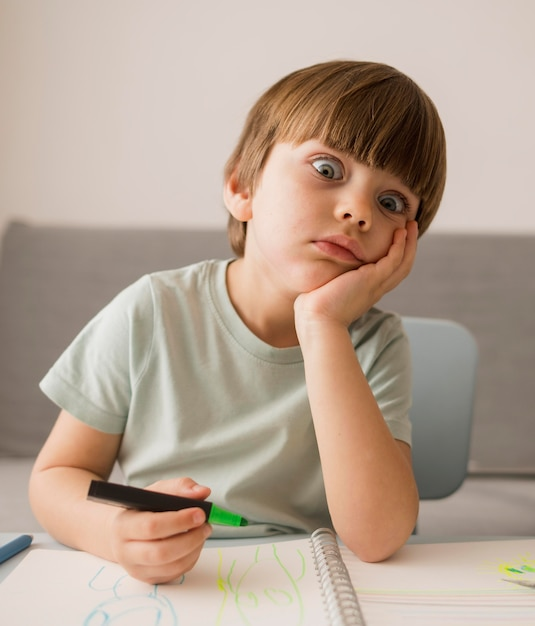 Vista frontale del bambino annoiato a casa mentre viene istruito Foto Gratuite