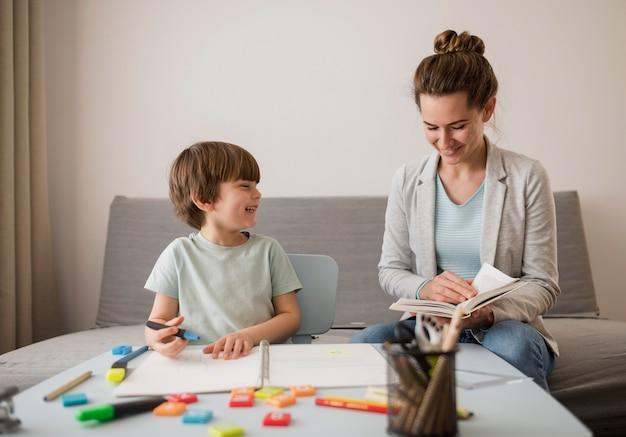 Vista frontale del bambino che è istruito a casa dalla donna Foto Gratuite