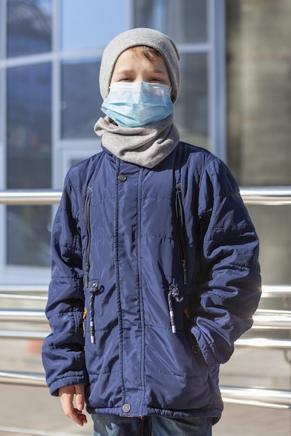 Vista frontale del bambino che indossa la maschera medica fuori Foto Gratuite