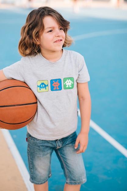 Vista frontale del bambino con il basket Foto Gratuite