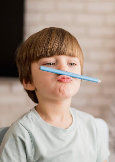 Vista frontale del bambino in posa sciocca durante la sessione di tutoraggio Foto Gratuite