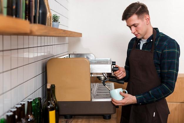 Vista frontale del barista che produce caffè espresso Foto Gratuite