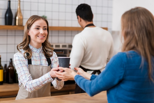 Vista frontale del barista dando caffè al cliente Foto Gratuite