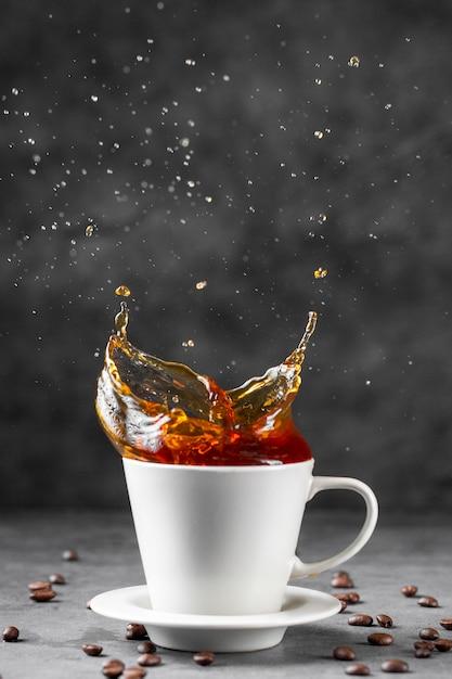 Vista frontale del caffè che spruzza in tazza Foto Gratuite