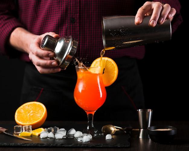 Vista frontale del cocktail di miscelazione dell'uomo Foto Gratuite