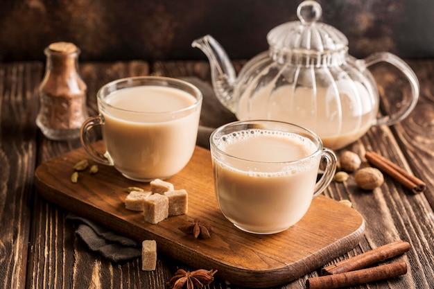 Vista frontale del concetto del tè al latte con cannella Foto Gratuite