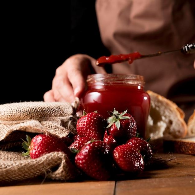 Vista frontale del cuoco unico con barattolo di marmellata di fragole Foto Gratuite