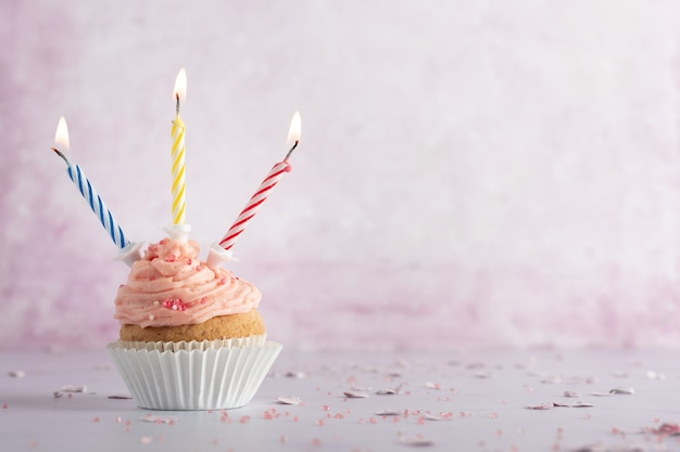 Vista frontale del cupcake compleanno con candele accese e copia spazio Foto Gratuite