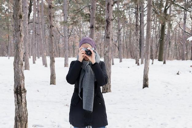 Vista frontale del fotografo donna con fotocamera in inverno Foto Gratuite
