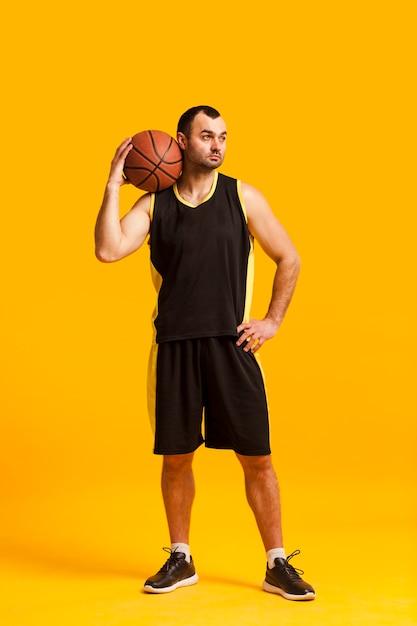Vista frontale del giocatore di pallacanestro maschio che posa con la palla sulla spalla Foto Gratuite