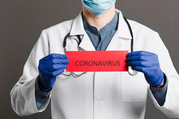 Vista frontale del medico con stetoscopio in possesso di carta con coronavirus Foto Gratuite