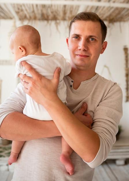 Vista frontale del padre che tiene neonato Foto Gratuite