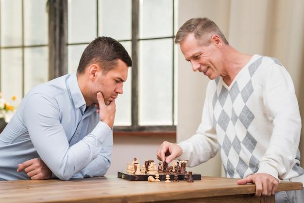 Vista frontale del padre e del figlio che giocano a scacchi Foto Gratuite