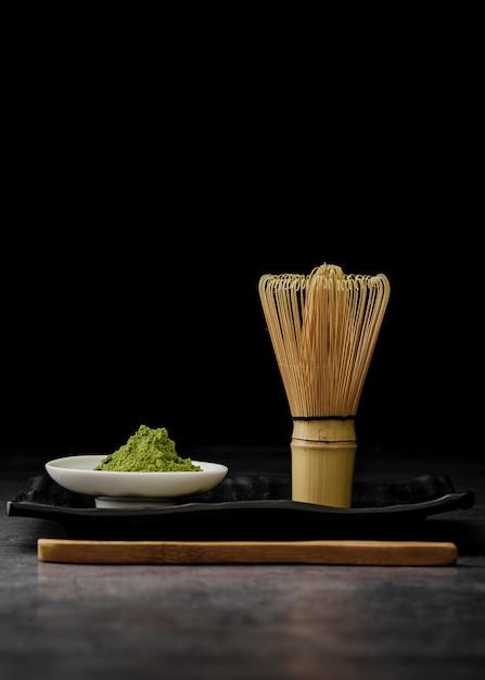 Vista frontale del tè matcha in polvere con frusta di bambù Foto Gratuite