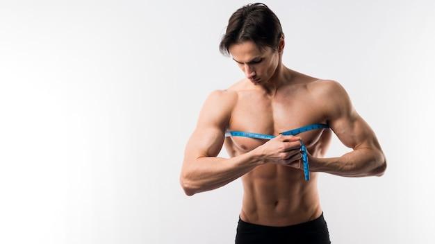 Vista frontale del torace di misurazione uomo muscoloso Foto Gratuite