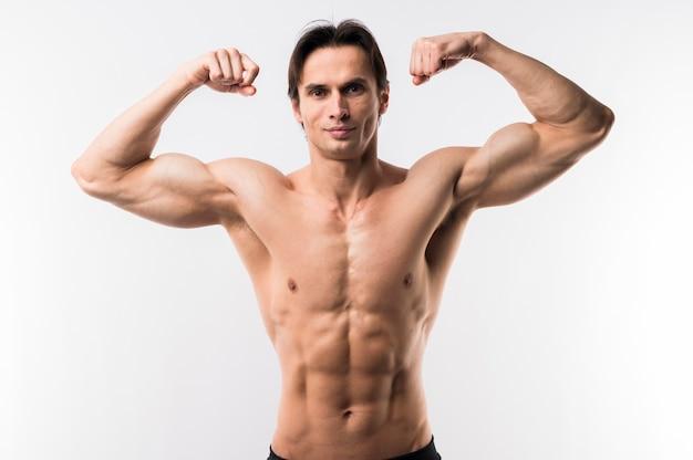 Vista frontale dell'uomo atletico che mostra il bicipite Foto Gratuite