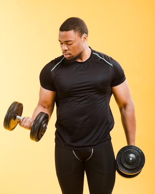 Vista frontale dell'uomo atletico che tiene i pesi in attrezzatura della palestra Foto Gratuite