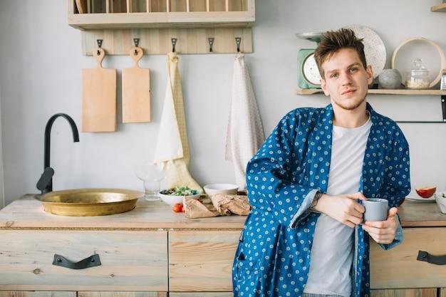 Vista frontale dell'uomo che esamina la tazza di caffè della tenuta della macchina fotografica in cucina Foto Gratuite