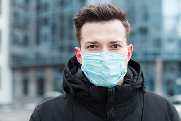 Vista frontale dell'uomo che indossa maschera medica nella città Foto Gratuite