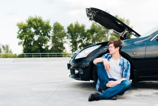 Vista frontale dell'uomo che si siede vicino all'automobile Foto Gratuite