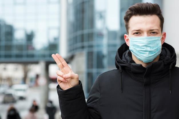 Vista frontale dell'uomo con coronavirus che indossa maschera medica nella città Foto Gratuite