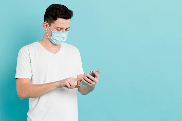 Vista frontale dell'uomo con la mascherina medica che esamina smartphone Foto Gratuite
