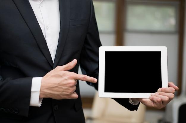 Vista frontale dell'uomo d'affari che indica alla compressa Foto Gratuite