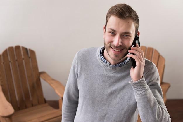 Vista frontale dell'uomo di smiley che parla sui telefoni Foto Gratuite