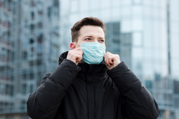 Vista frontale dell'uomo in città indossando maschera medica Foto Gratuite