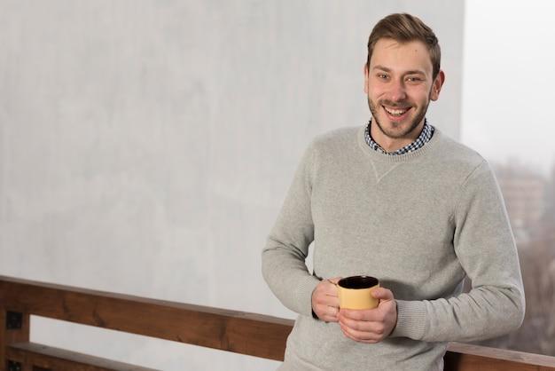 Vista frontale dell'uomo in maglione che tiene tazza in mano Foto Gratuite