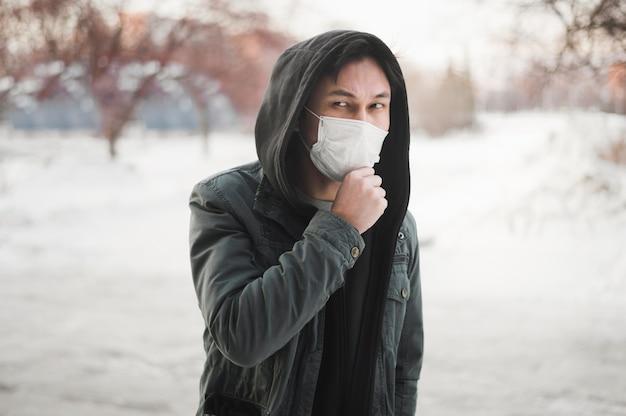 Vista frontale dell'uomo in posa mentre indossa una maschera medica Foto Gratuite