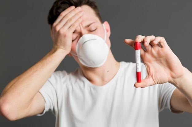 Vista frontale dell'uomo malato che indossa una maschera medica e che tiene vacutainer Foto Gratuite