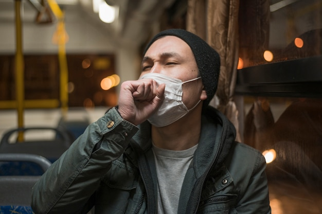 Vista frontale dell'uomo malato che tossisce nell'autobus mentre indossando maschera medica Foto Gratuite