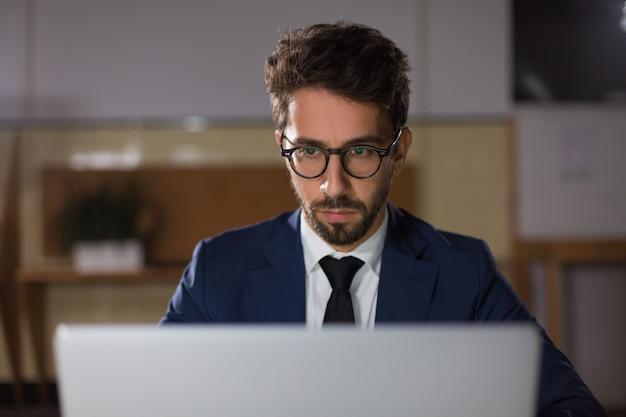 Vista frontale dell'uomo premuroso in occhiali che esaminano computer portatile Foto Gratuite
