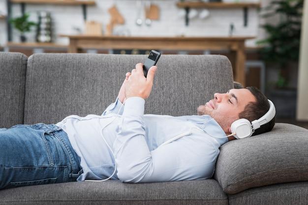 Vista frontale dell'uomo sdraiato sul divano Foto Gratuite