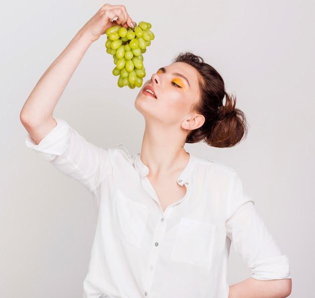 Vista frontale della bella donna con uva Foto Gratuite