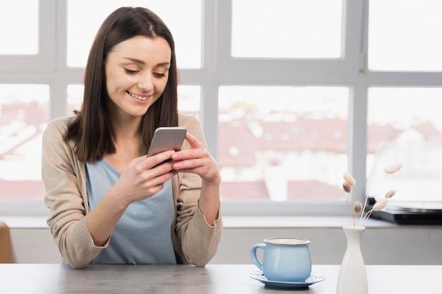 Vista frontale della donna allo smartphone della tenuta dello scrittorio Foto Gratuite