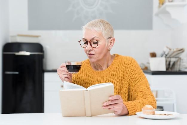 Vista frontale della donna anziana che legge un libro e che tiene la tazza di caffè Foto Gratuite