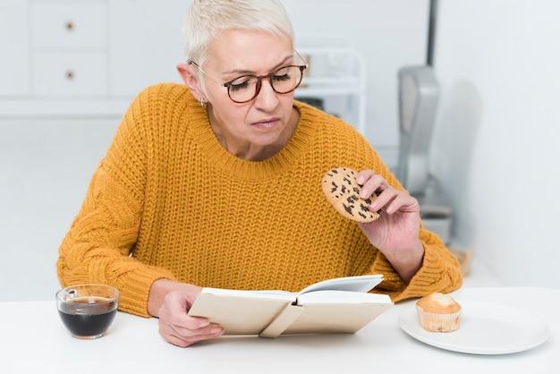 Vista frontale della donna anziana che tiene grande biscotto e libro di lettura Foto Gratuite