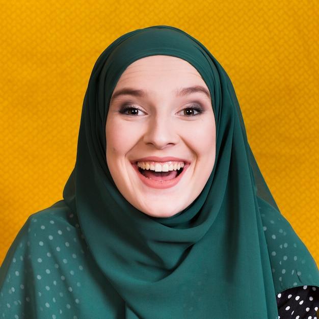 Vista frontale della donna araba allegra sul contesto giallo Foto Gratuite