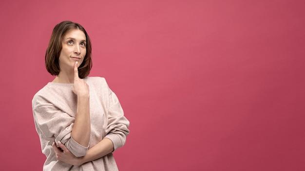 Vista frontale della donna che colpisce una posa di pensiero Foto Gratuite