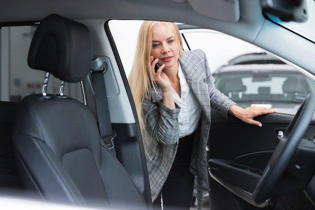 Vista frontale della donna che controlla l'interno dell'automobile Foto Gratuite
