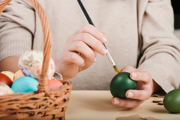 Vista frontale della donna che decora le uova di pasqua Foto Gratuite