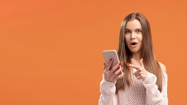 Vista frontale della donna che indica allo smartphone che sta tenendo Foto Gratuite
