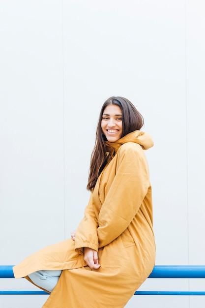 Vista frontale della donna che indossa giacca gialla che si siede sulla ringhiera blu Foto Gratuite